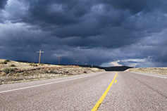 Dark clouds above empty road