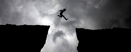 Man jumping from cliff amongst dark clouds