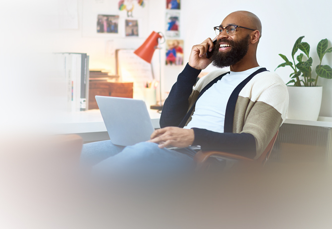 Man talking on mobile phone with laptop