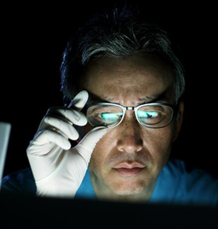 Man with gloves adjusting glasses looking at screen