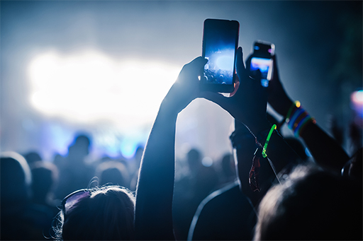 People taking pictures on mobile phones at a concert