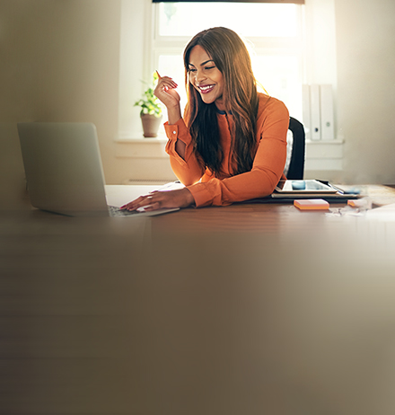 Woman smiling while looking at laptop