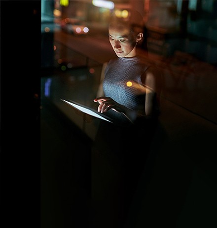 Woman using tablet at night standing near glass window