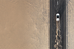 Aerial view of white car on a deserted highway running on high speed