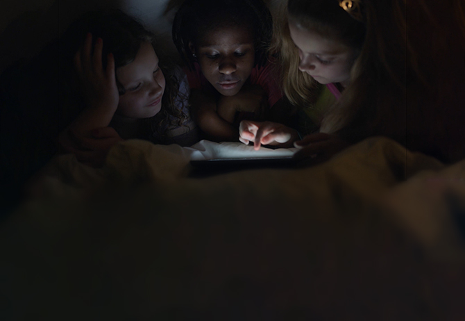 Three kids using a tablet in bed