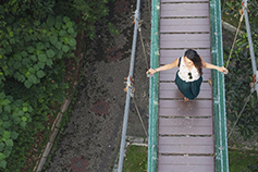 Top-view - Woman walking on wooden hanging bridge