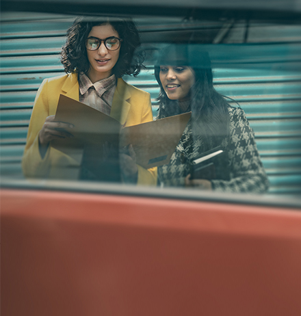 Outdoor image of two happy businesswomen discussing project