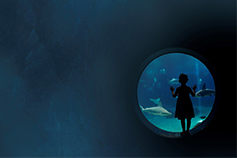 Girl standing near a round window looking at fishes in aquarium