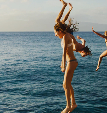 Group of girls enjoying outdoors and diving in an ocean
