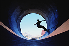 Silhouette of man skateboarding in tunnel