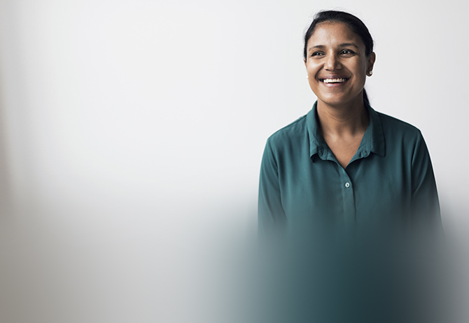 Happy adult woman looking away while standing against white background