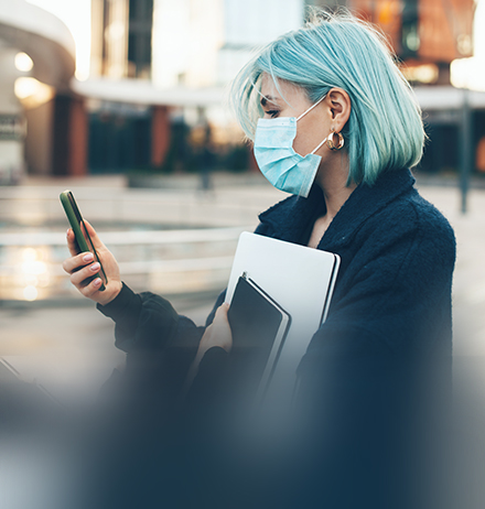 Caucasian woman with blue hair is chatting with someone while wearing a protective mask