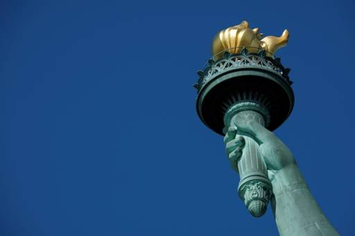 The hand of the statue of liberty, holding a torch, against a blue sky