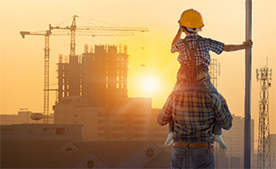 Boy on father shoulder overlooking construction site