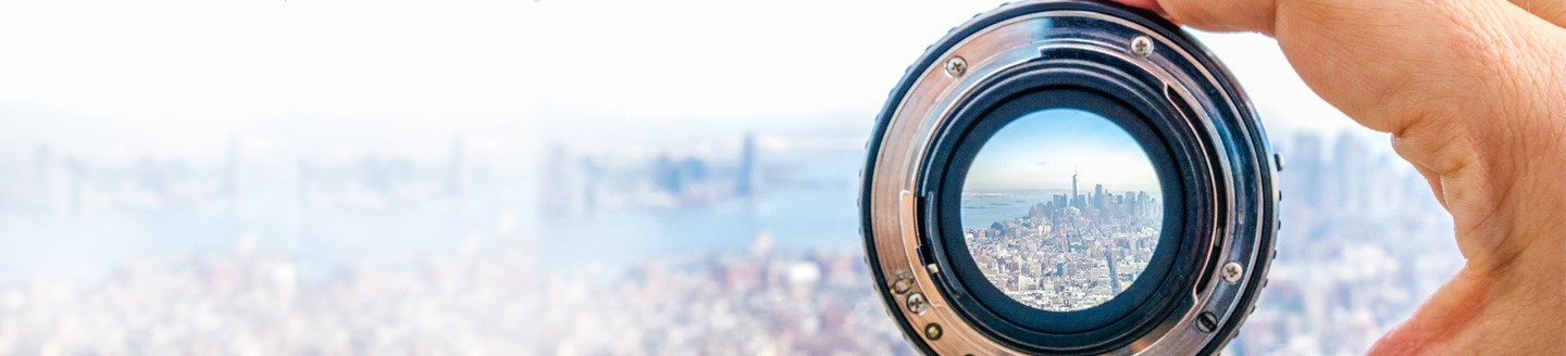 Human hand holding camera lens capturing city view