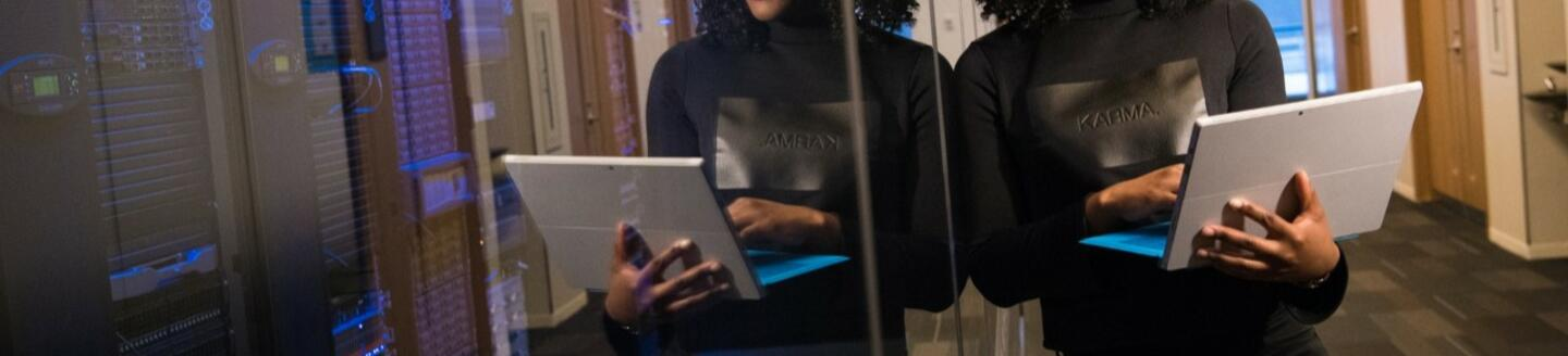 woman-in-black-long-sleeved-top-holding-laptop