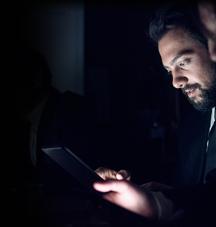 Risk Assurance and Internal Audit - Man in dark with tablet