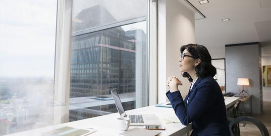 Business woman sitting in office with laptop looking out of window