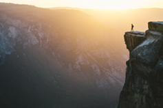 Man standing on mountain cliff at sunrise