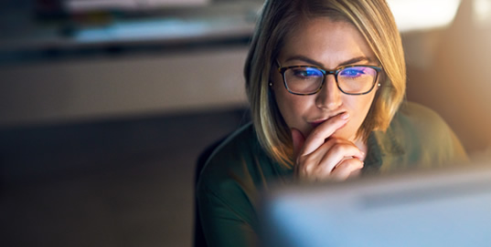 Woman wearing spectacles, deep thinking while looking at screen