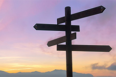 Navigation sign in front of purple sky.