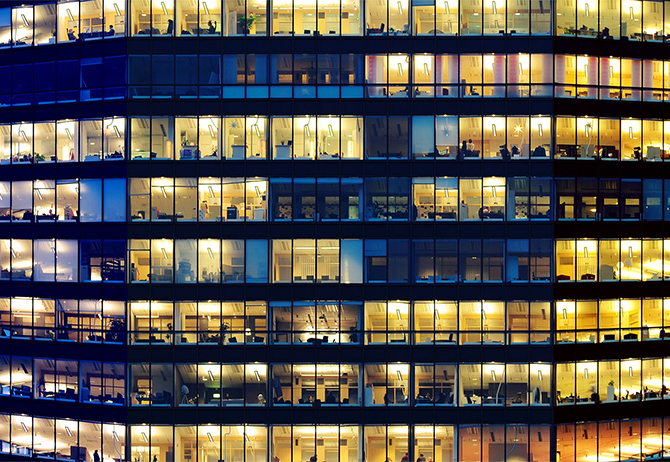 People working behind glass windows in office tower