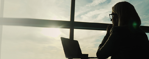 Silhouette of woman looking at laptop