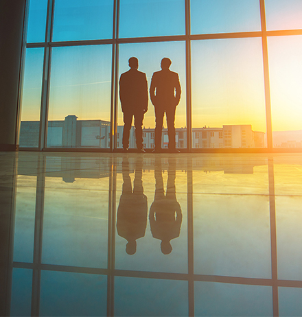 Two businessmen standing at office glass window at sunset