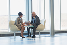 two businesspeople sitting and discussing in office
