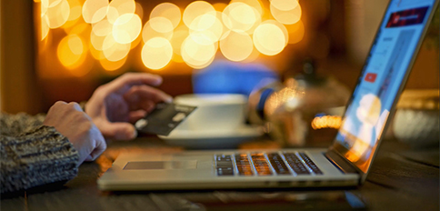 Side view of a person typing on laptop while doing  a payment with credit/debit card