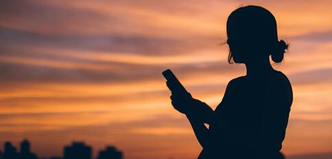 Silhoutte of women using cell phone against evening sky