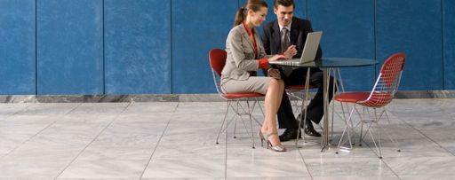 Two business people looking at laptop infront of map wall