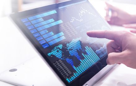 Finger touching screen with financial analytics