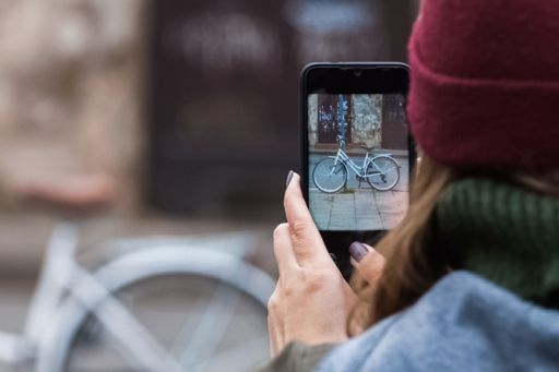 woman with mobile phone photographing bicycle