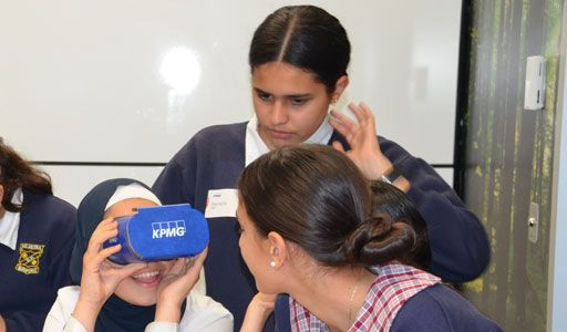 three girls looking in google glasses with KPMG logo