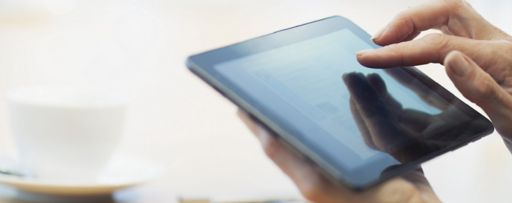 KPMG IFRS toolkit topic image: person using a digital tablet and a stack of reference manuals