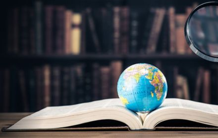 Globe on open book with magnifying glass in front of bookshelves
