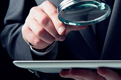 Man holding magnifying glass over screen