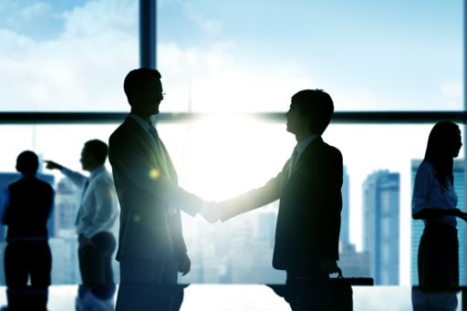 Business men shaking hands to confirm deal