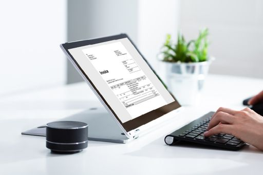 person putting invoice in bookkeeping on laptop