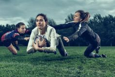 Girls playing rugby in suit