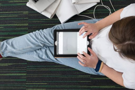 Woman sitting by bookshelves searching on iPad