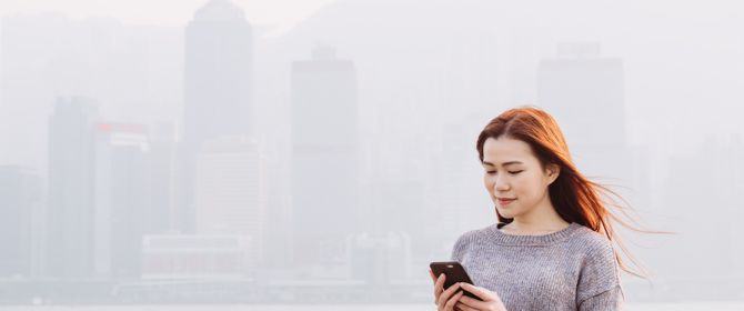 Woman standing and using her mobile phone