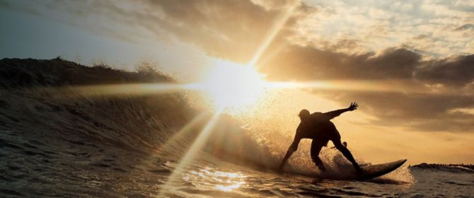 A man surfing at sunset
