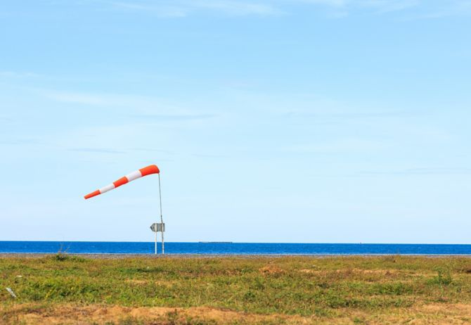 A wind force against the dark sea and blue sky