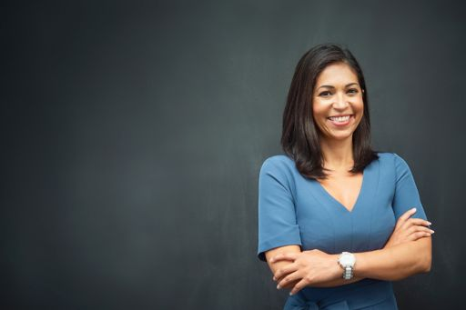 A woman smiling in front of a grey background