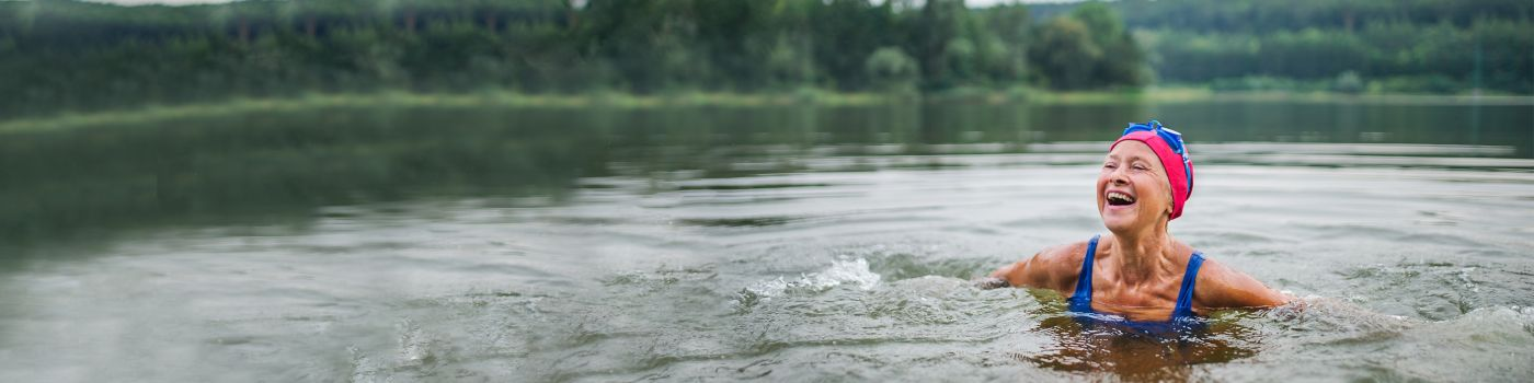 Active senior woman swims in a lake