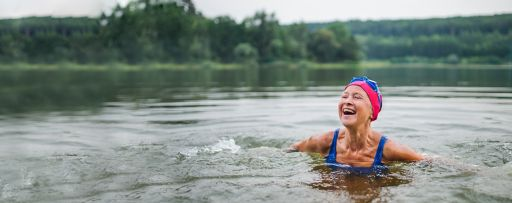 An active senior woman swims in a lake