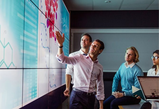 Adults viewing data on a huge screen