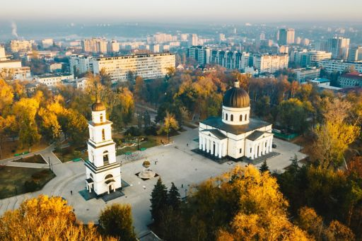 Aerial view of city of Moldova with yellow trees around white building
